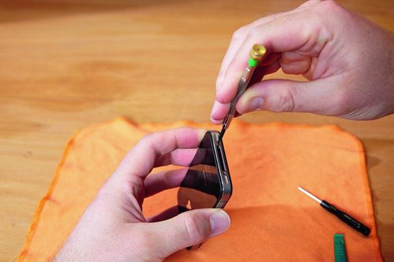 Чтобы поменять батарею, нужно снять винты, запирающие заднюю панель iPhone 4x