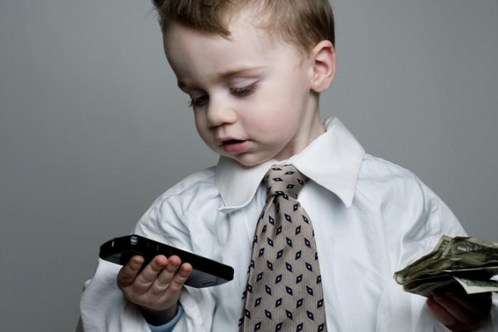 Мальчик в галстуке держит в одной руке айфон, в другой деньги