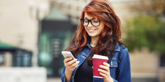 Девочка в очках смотрит на телефон